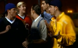 """Overalls, flashy jackets, backwards cap, football jersey. Yep, story checks out, it's the quintessential boy band."""